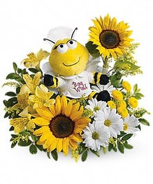 A plush bumblebee surrounded by sunflowers, daisies and alstromeria lilies.