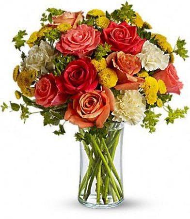 Orange and coral roses with yellow carnations and button mums in a glass vase.