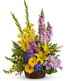 Pastel pink, blue and bright yellow flowers in a sympathy basket presentation.