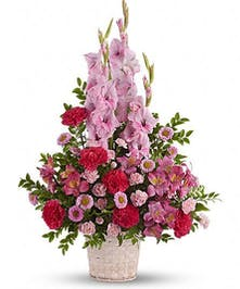Basket filled with a mix of pink flowers in a sympathy arrangement.