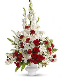White and red flowers in a white urn for sympathy or funeral service.