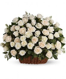 An abundance of white roses in a sympathy basket presentation.
