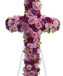 Floral sympathy cross of purple and lavender flowers.