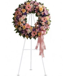 Sympathy wreath with peach, lavender and pink flowers and coordinating ribbon.