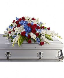 Casket flowers made of blue delphinium, red roses and white flowers for a patriotic tribute.