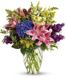 Hydrangea and stargazer lilies in a clear glass vase.
