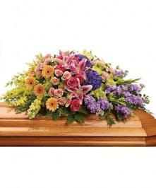 Rainbow casket spray of pink, orange, purple and green flowers with greenery.