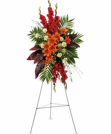 Radiant sympathy spray of red and orange flowers and greenery.