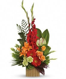Orange roses and lilies, green anthuriums and red gerbera daisies and greenery in a bamboo cube vase.