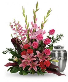 Urn arrangement of hot pink, red and pink flowers with greenery.
