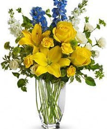 Yellow and blue flowers in a clear glass vase.