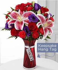 Flower bouquet of hot pink mini carnations, orange Gerbera daisies, yellow Asiatic lilies and pink alstroemeria in a hot pink glass vase.