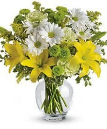 Yellow lilies, white daisies and green carnations in a clear glass vase.