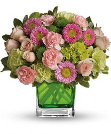 Pink and green mixed flowers in a cube vase.