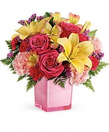 Roses, lilies, alstromeria, carnations and leatherleaf fern in a one-sided flower arrangement.