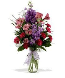 purple, pink and red flowers in a glass vase decorated with a purple bow.