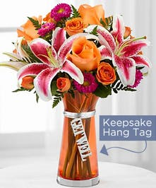 Orange roses and spray roses, stargazer lilies and matsumoto aster flowers in an orange glass vase.