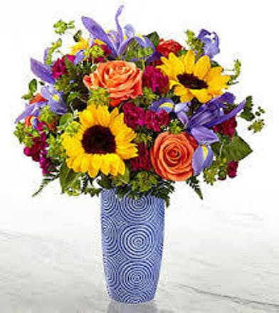 Sunflowers, orange roses, blue iris and violet mini carnations in a blue vase with swirl accent.