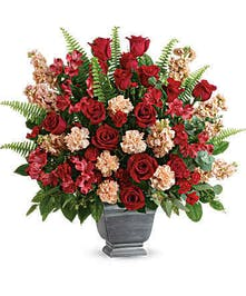 Sympathy arrangement of red roses, greenery and more in a large stone-look pot.