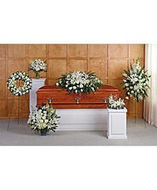 A set of six all-white sympathy flower arrangements.