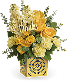 Yellow roses, stock and carnations in a gold cube vase.