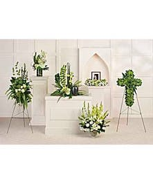 A collection of six sympathy flower arrangements in white and green.