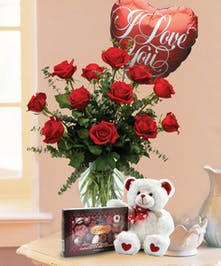 One dozen red roses accompanied by a heart-shaped mylar balloon that says I Love You, white stuffed bear and box of chocolates.