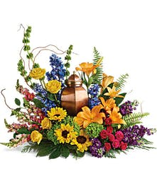 Bright arrangement of hydrangea, roses and sunflowers to surround an urn.