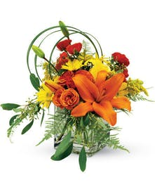 orange and yellow lily and daisy arrangement in cube vase
