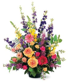 Arrangement of vibrant seasonal sympathy flowers.