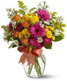 Hot pink, yellow, orange and red flowers in a clear glass vase tied with a bow.