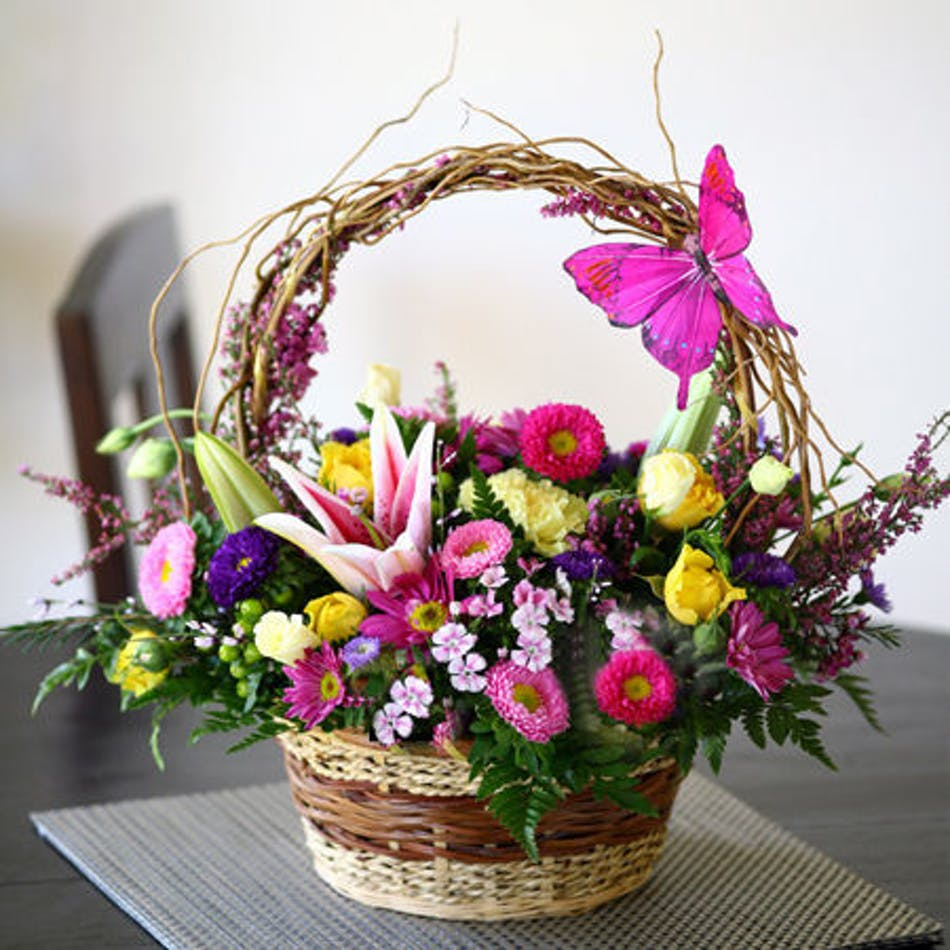 Brown wicker basket with aster, heather, waxflower, stargazer lily, roses, carnations, and daisies accented with a butterfly decoration.