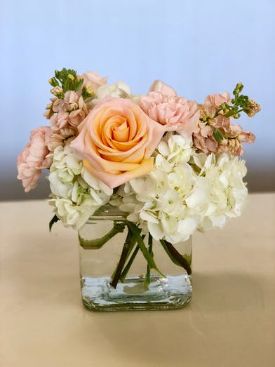 Peach and white flowers in a clear glass cube vase.