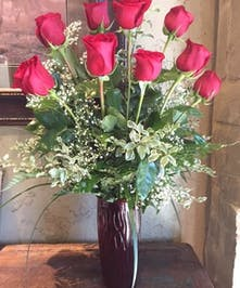 One dozen red roses and baby's breath flowers in a vase