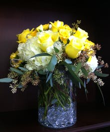 Yellow roses, hydrangea and crystal accents in a clear glass vase.