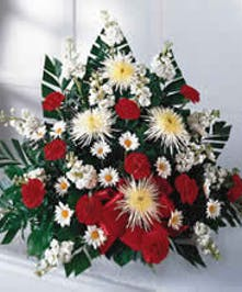 Traditional sympathy design of white and red flowers with greenery.