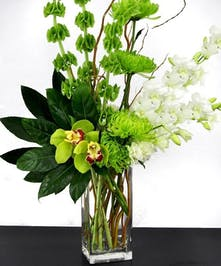Modern flower bouquet in shades of green and white in a tal glass cube vase.