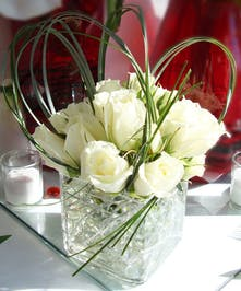 Luxury in a clear cube vase filled with winter white roses and artistic greenery.